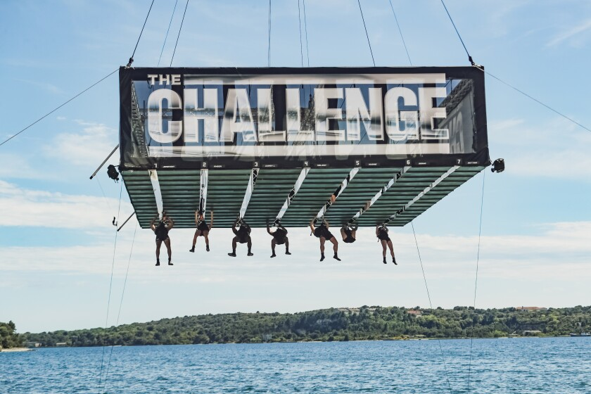 """Competitors hang from a platform suspended over water labeled with the words """"THE CHALLENGE"""""""
