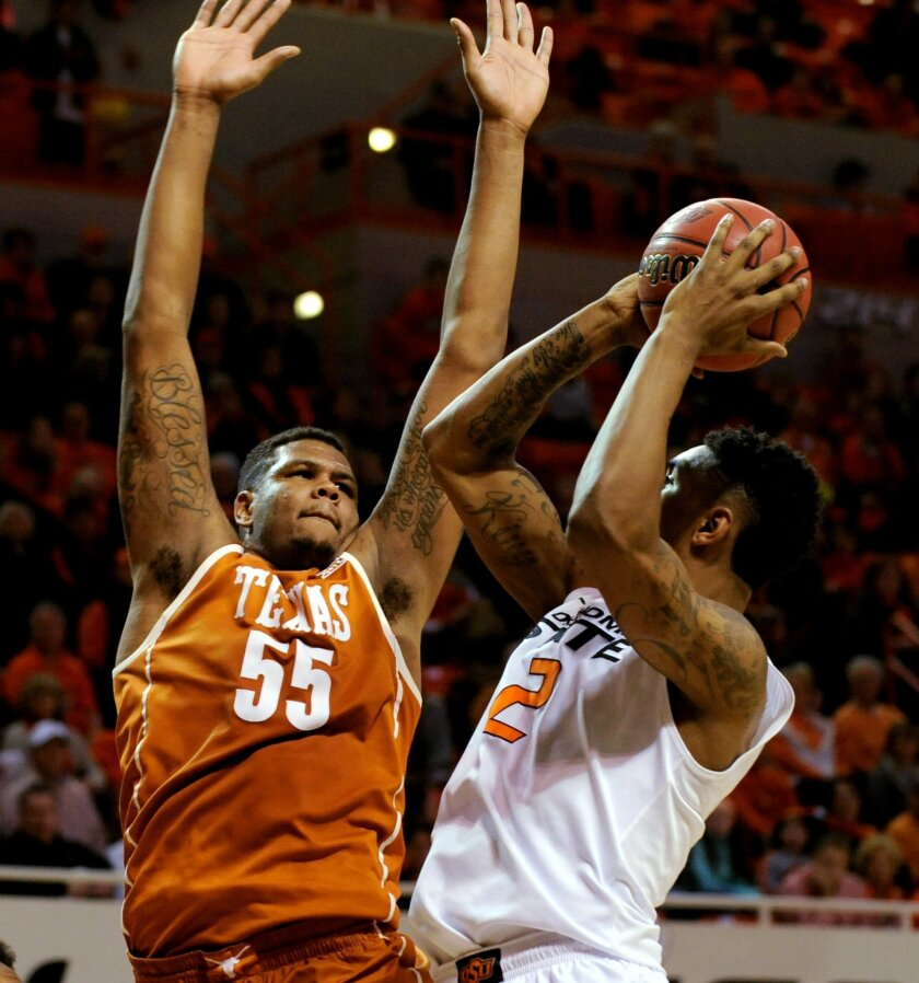 Texas center Cameron Ridley (55) defends against a shot by Oklahoma State forward Le'bryan Nash (2) during the first half of an NCAA college basketball game in Stillwater, Okla., Saturday, Jan. 10, 2015. (AP Photo/Brody Schmidt)