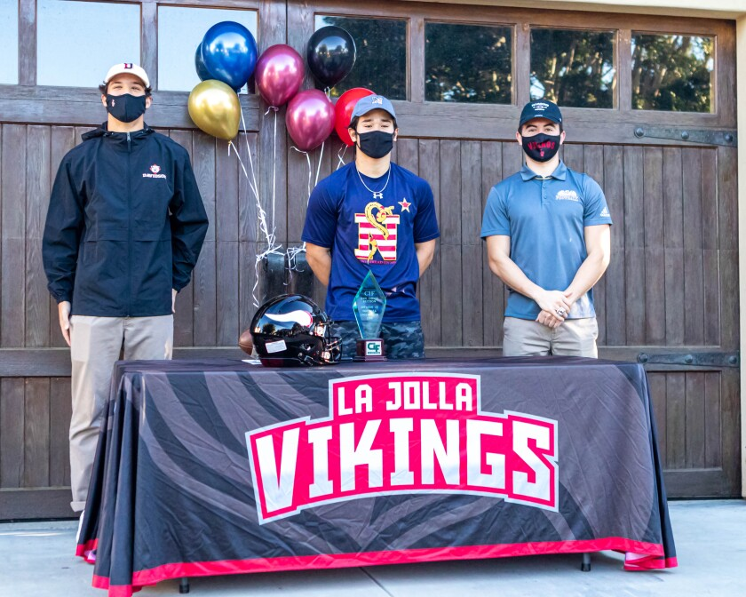 Viking football players (from left) Alessandro Demoreno, Max Smith and Diego Solis sign letters of intent.