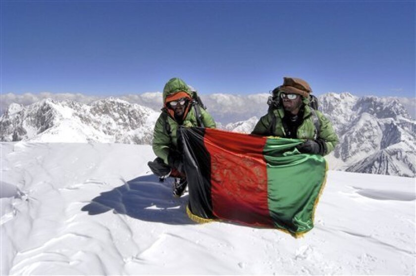 In this July 19, 2009 photo provided by Louis Meunier of Taimani Films, Amruddin Sanjar and Malang Daria hold the Afghan national flag on top of Afghanistan's highest mountain, Noshaq. (AP Photo/Taimani Films)