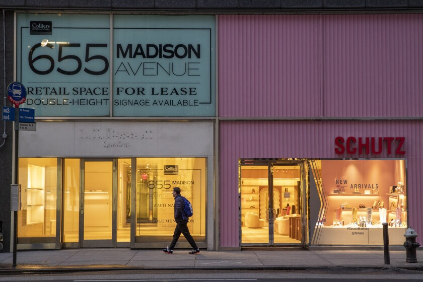 A pedestrian walks along Madison Avenue in New York.