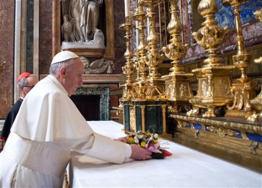 CORRECTS YEAR TO 2013 - In this photo provided by the Vatican newspaper L'Osservatore Romano, Pope Francis puts flowers on the altar inside St. Mary Major Basilica, in Rome, Thursday, March 14, 2013. Pope Francis opened his first morning as pontiff by praying Thursday at Rome's main basilica dedica