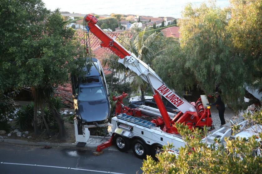 Una grúa baja a un auto que se estrelló en Palos Verdes Drive y terminó sobre el techo de una casa en Palos Verdes Estates, California, el miércoles 3 de febrero de 2016. (Chuck Bennett/Daily Breeza vía AP)