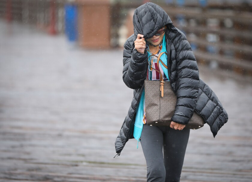 Evelyn Ramos battles the wind and rain during a visit to the Oceanside Pier, November 20, 2019 in Oceanside, California.