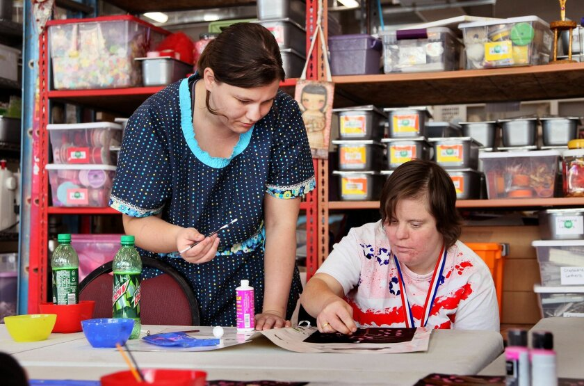 Charity Wings Art & Craft Center volunteer instructor Christina Popp stands over Marcy Hedlind from the TERI Campus of Life organization for people with special needs as she works on an art project at the center.