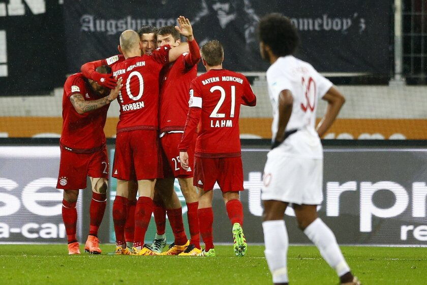 Bayern's Robert Lewandowski, background center, celebrates with teammates after scoring his side's opening goal during the German first division Bundesliga soccer match between FC Augsburg and FC Bayern Munich at the WWK Arena in Augsburg, Germany, Sunday, Feb. 14, 2016. (AP Photo/Matthias Schrader
