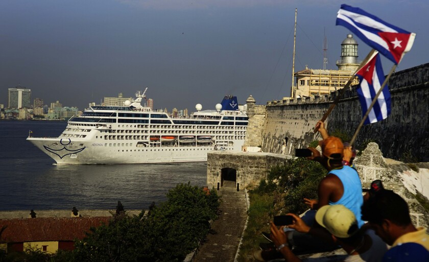 People waving Cuban flags greet passengers on Carnival's Adonia cruise ship as they arrive in Havana on Monday.