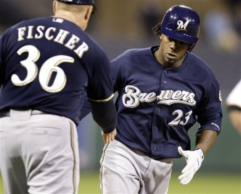 Milwaukee Brewers' Rickie Weeks (23) rounds third as he is congratulated by coach Brad Fischer (36) after hitting a ninth-inning thee-run home run off Pittsburgh Pirates closer Matt Capps in a baseball game in Pittsburgh on Monday, May 4, 2009. The Brewers won 7-4. (AP Photo/Gene J. Puskar)
