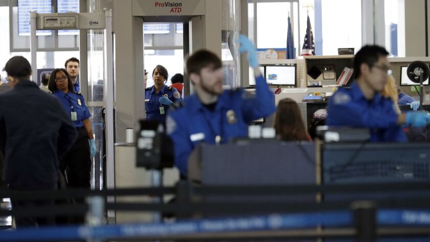 FILE- In this Jan. 5, 2019, file photo Transportation Security Administration officers work at a che