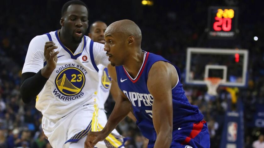 Clippers' C.J. Williams, right, drives against Golden State Warriors' Draymond Green during the first half on Wednesday.