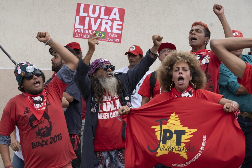 "Supporters of former President Luiz Inacio Lula da Silva of Brazil gather Nov. 8 and shout ""Free Lula"" outside the Federal Police headquarters in Curitiba where Lula is imprisoned."