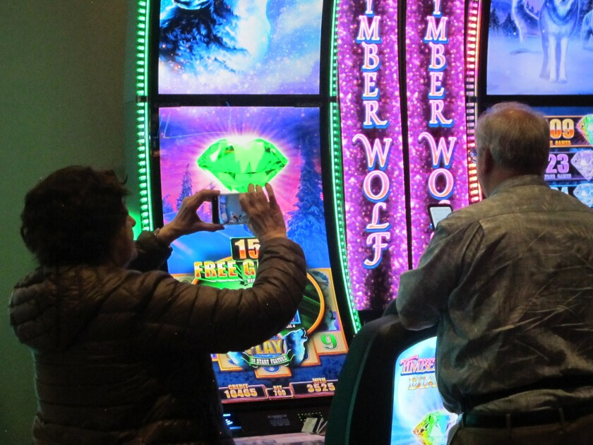 A woman takes a cell phone photo of a slot machine at Bally's casino in Atlantic City, N.J., on June 23, 2021. On Friday, July 16, 2021, New Jersey gambling regulators released figures showing the nine casinos won $345 million from gamblers in June. (AP Photo/Wayne Parry)