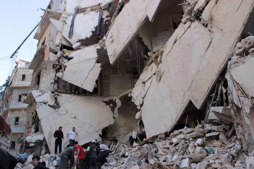 Syrian rescue workers and civilians inspect the rubble after an airstrike, reportedly by government forces, on the rebel-held Bustan Qasr neighborhood of Aleppo.