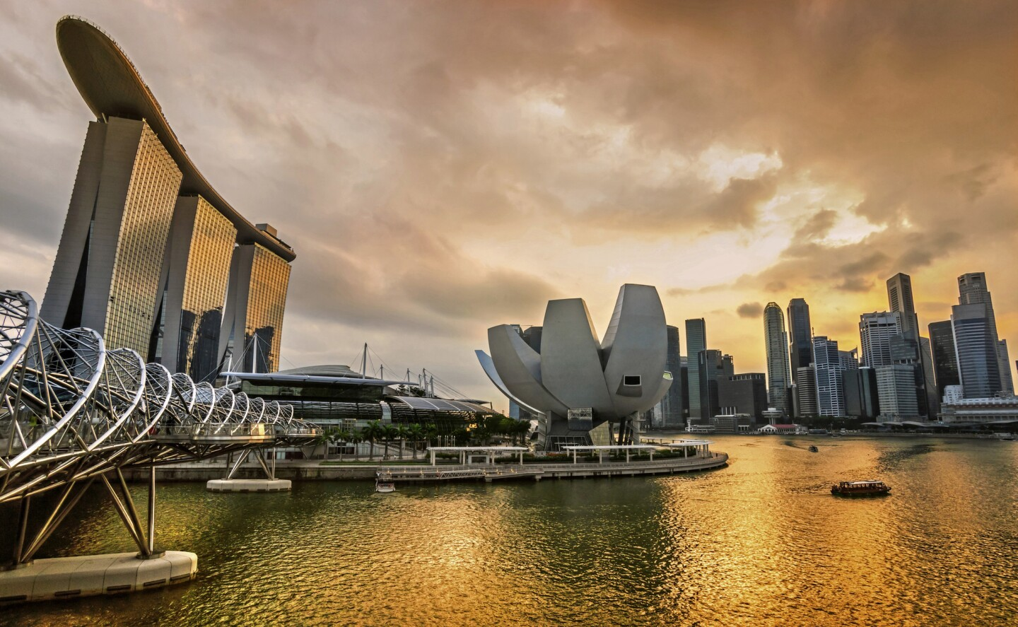 The dramatic Singapore city skyline at sunset, with the striking Marina Bay Sands Hotel to the left, three towers with a Skypark atop them. On Aug. 9, 2015, Singapore celebrates its golden jubilee.