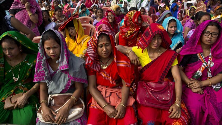 Indian tribal women in traditional attire listen to Congress party president Rahul Gandhi at an elec