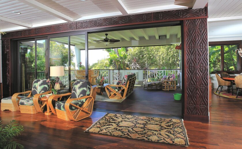 The first floor has a great room with a large sliding door that connects it to an outdoor seating area and lanai.