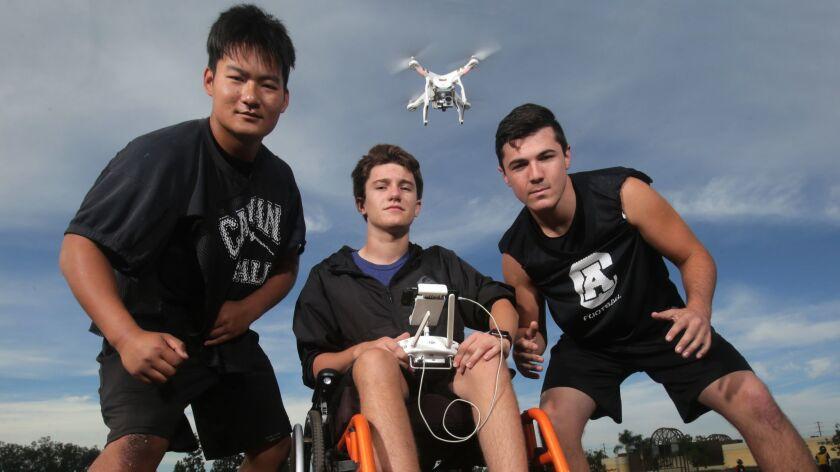Classical Academy football team members, from left, Cody Schaefer, Matthew Tillyer, flying the drone