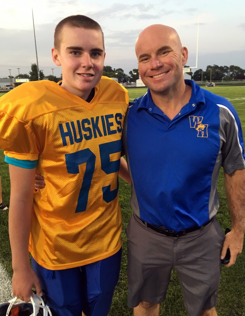 In this photo taken Monday, Sept. 16, 2019 and provided by the Hoffman family, Jack Hoffman and his father Andrew Hoffman poses before a football game in Atkinson, Neb. Hoffman, who suffers from pediatric brain cancer and who scored a touchdown at a Nebraska practice game, is playing football for real. Now 13, Hoffman took the field Monday to play center for his junior high team in Atkinson, Neb. (Brianna N. Hoffman via AP)
