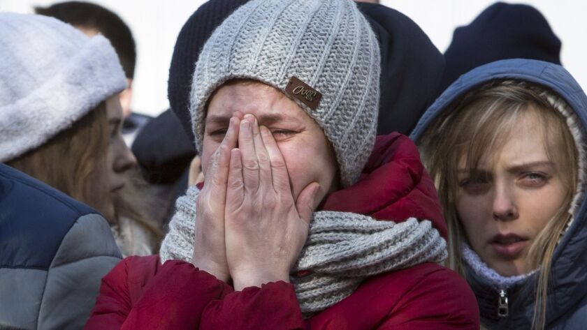 A woman reacts on March 26, 2018, after laying flowers for the victims of a fire in a multi-story shopping center in the Siberian city of Kemerovo, Russia.