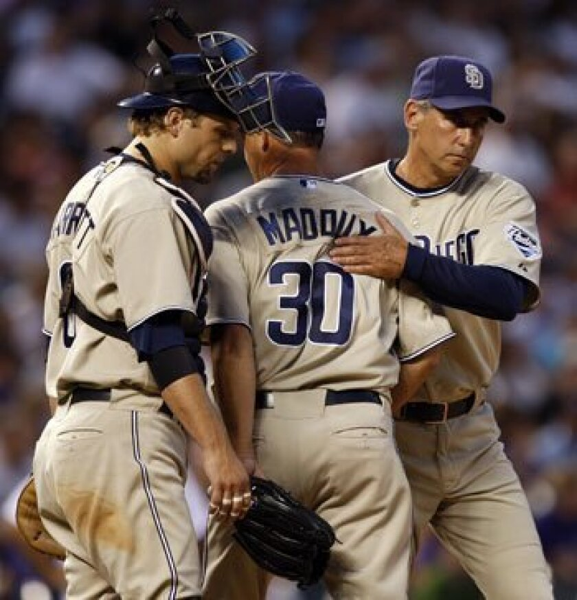 Padres catcher Michael Barrett looks down as starting pitcher Greg Maddux is pulled from the game by manager Bud Black in the fifth inning against the Colorado Rockies in Denver Monday night.