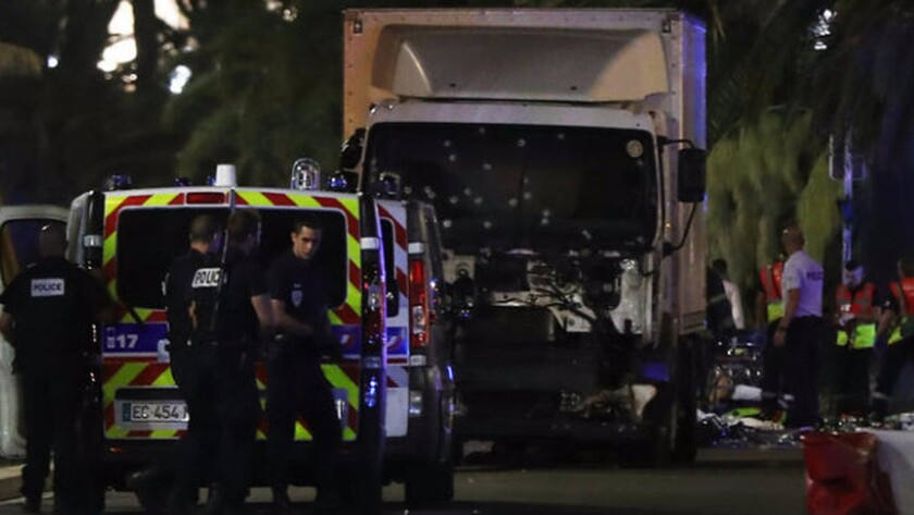 Police officers and rescue workers stand near a truck that plowed into a crowd leaving a fireworks display in Nice, France, on July 14.