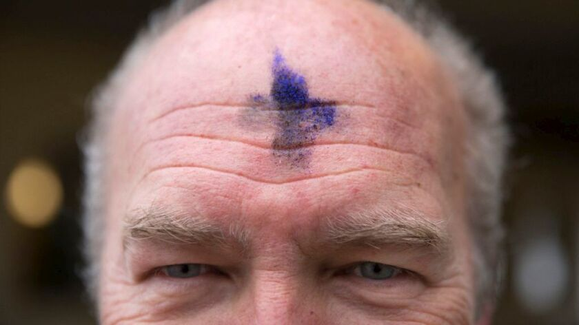 Jon Grondahl of Unity Lutheran Church in Chicago is marked with a cross of ashes mixed with purple glitter for Ash Wednesday. The glitter is a sign of support for the LGBTQ community.
