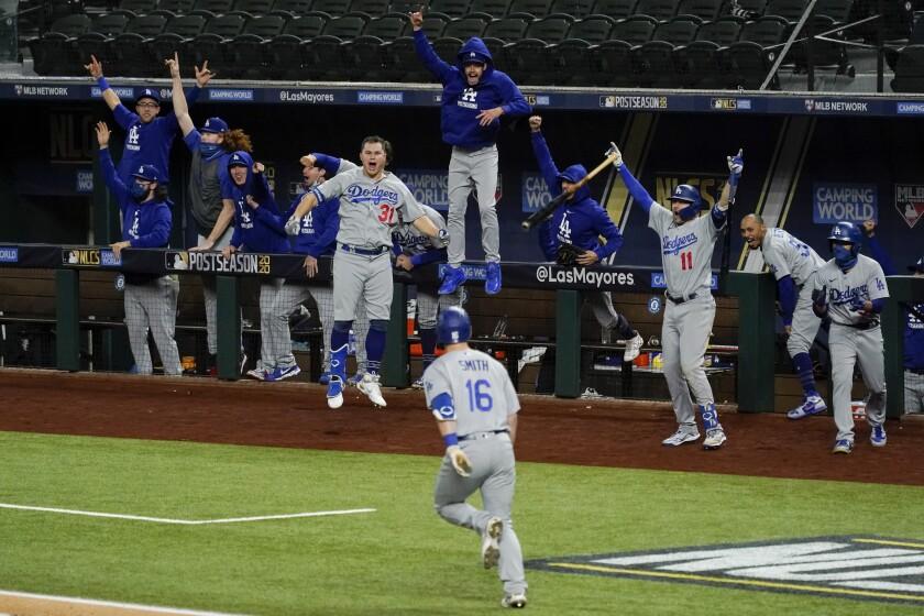 Los Dodgers de Los Ángeles festejan un jonrón de tres carreras de Will Smith, en el quinto juego de la Serie de Campeonato de la Liga Nacional ante los Bravos de Atlanta, el viernes 16 de octubre de 2020, en Arlington, Texas (AP Foto/Tony Gutiérrez)