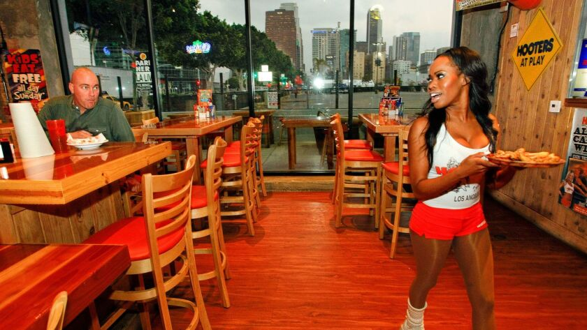 Customer Matt Thomas sits at a table at a Hooters restaurant in Los Angeles as employee Keiana Martinez delivers a meal to another customer. The Hooters chain was sued because its website did not comply with the Americans with Disabilities Act.