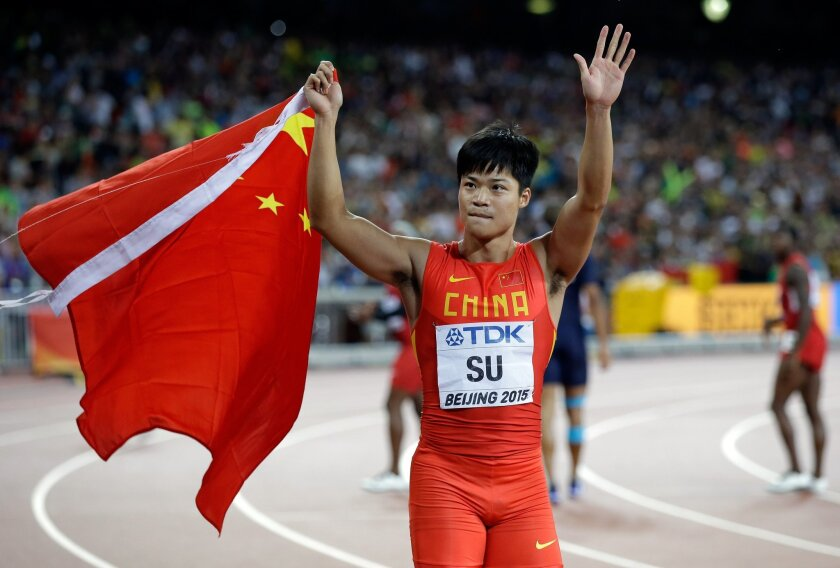 China's Su Bingtian waves to supporters after competing in the the men's 100m final at theWorld Athletics Championships at the Bird's Nest stadium in Beijing, Sunday, Aug. 23, 2015. Su is the first Chinese to participate in a 100m world championships final. (AP Photo/Kin Cheung)