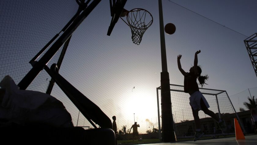 FILE- In this May 12, 2014 photo, a girl shoots baskets during team practice at a private sports clu