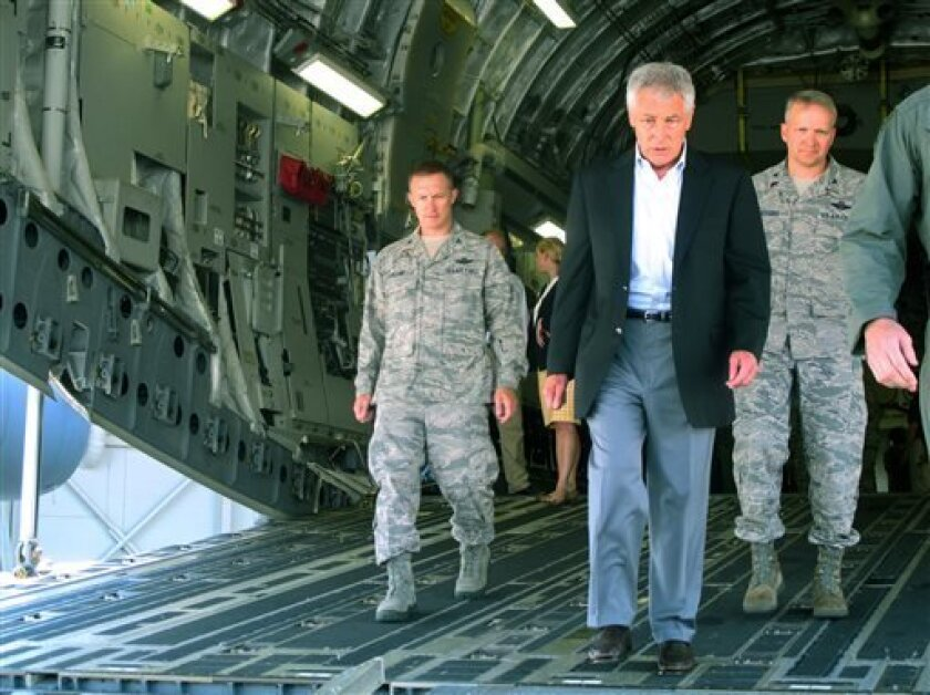 In this photo taken July 17, 2013, Defense Secretary Chuck Hagel, flanked by Air Force personnel, walks down the rear ramp of a C-17 at Joint Base Charleston near Charleston, S.C., on the last day of a three-day trip to visit bases in the Carolinas and Florida. When Hagel told civilian Department o