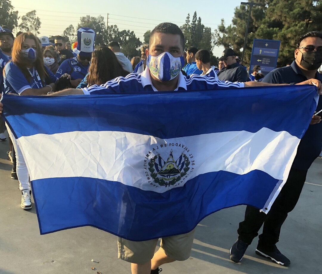 A Salvadoran fan holds a flag during a rally before the Salvadoran-Costa Rica soccer match