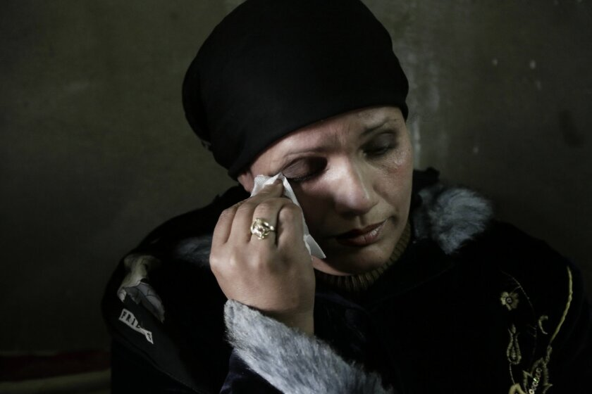In this Thursday, March 3, 2016 photo, Fadya Shehata Moussa, the mother mother of 17-year-old Bassem Amgad Hanna, one of four teens convicted for contempt of Islam, wipes away tears during an interview in Bani Mazar, Minya province, Egypt. The four teens and their supervisor, who was forced to leav