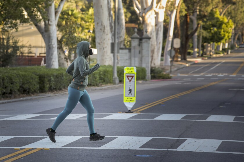 A jogger crosses the street wearing a face mask at Pomona College in March