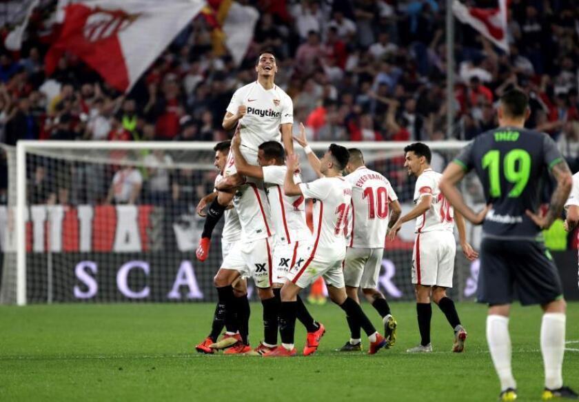 El delantero francés del Sevilla Wissam Ben Yedder (arriba) es felicitado por sus compañeros tras marcar su tercer gol ante la Real Sociedad, durante el partido de Liga en Primera División que disputaron en el estadio Sánchez Pizjuán, en Sevilla. EFE