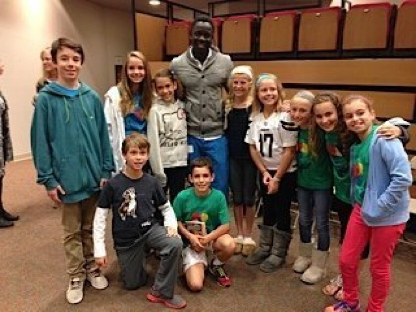 """(Above) Deng Abiel, one of """"The Lost Boys of Sudan,"""" with R. Roger Rowe students Grayson Hutchinson, Gaby Cary, Joshua Brown Ederly, Malia Riviere, Sam Haas, Sawyer Simo, Victoria Williams, Christian Braswell, Sofia Symon, and Grace Smith. (Below) Deng Abiel speaking to R. Roger Rowe students. Cour"""