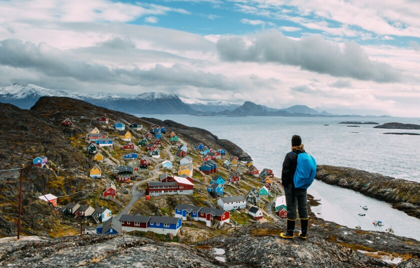 A visitor stops to look at the signature colorful houses of Kangmiut, a coastal village in Greenland.