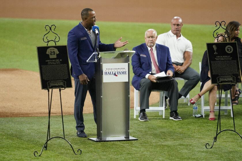 Retired Texas Rangers player Adrian Beltre, left, speaks as team public address announcer Chuck Morgan, center rear, looks on during a ceremony before a baseball game against the Oakland Athletics in Arlington, Texas, Saturday, Aug. 14, 2021. Beltre and Morgan were inducted into the Rangers' Hall of Fame on Saturday. (AP Photo/Tony Gutierrez)