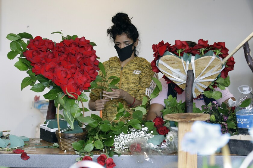 FILE - In this May 10, 2020, file photo, a merchant prepares a floral arrangement on Mother's Day at the Los Angeles Flower Market in Los Angeles. Americans are more unhappy today than they've been in nearly 50 years. That's according to the COVID Response Tracking Study, conducted in late May by NORC at the University of Chicago. (AP Photo/Marcio Jose Sanchez, File)