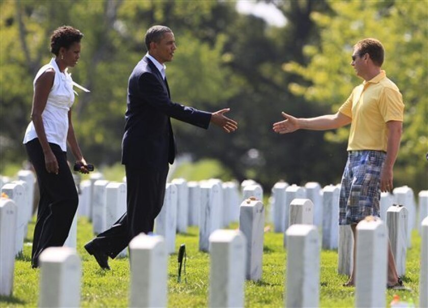 President Barack Obama extends a hand to an unidentified visitor to Section 60 in Arlington National Cemetery Saturday, Sept. 10, 2011, in Arlington, Va., as he and first lady Michelle Obama, left, pay their respects to those who have made the ultimate sacrifice over the past decade. Sunday will mark the 10th anniversary of the Sept. 11 attacks. (AP Photo/Carolyn Kaster)