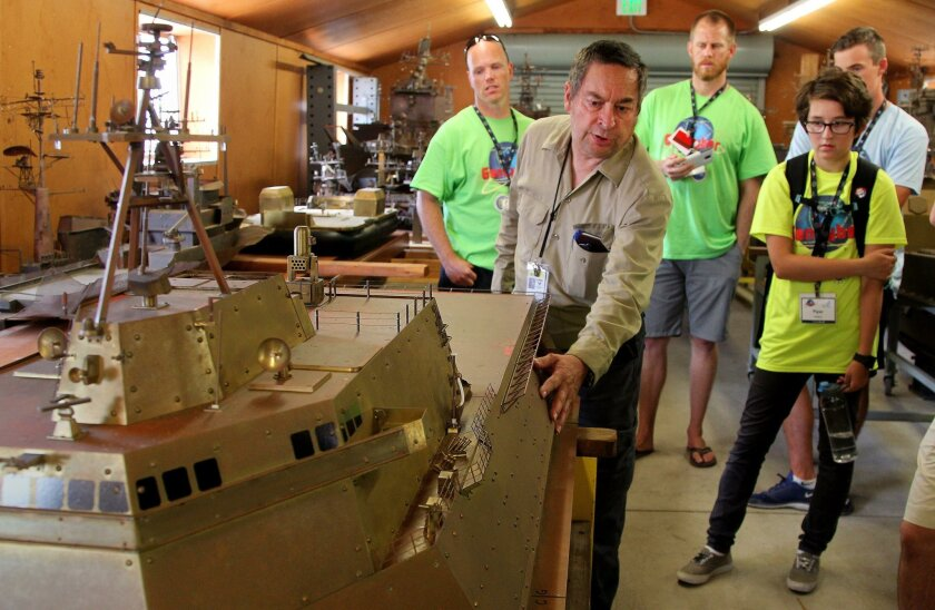 SPAWAR electronic technician Daryl Vonmueller shows students a scale model of a Littoral Combat Ship that will be used to test shipboard antennas. The students visited SPAWAR during a field trip while taking a weeklong class on cyber security at the University of San Diego.