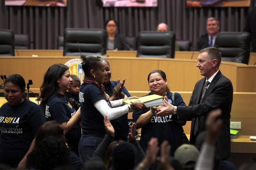 Latrice Gamble is seen handing a binder full of petitions to L.A. Unified Supt. John Deasy in hopes of invoking the controversial parent trigger law for the 24th Street Elementary School.