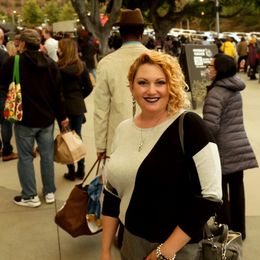 A woman poses for a photo, a line of people behind her.