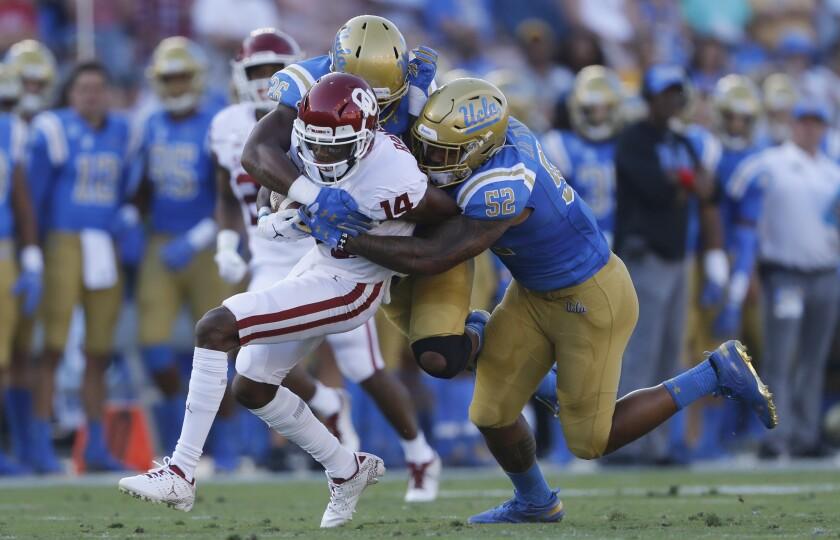 UCLA's Lokeni Toailoa, right, and Leni Toailoa tackle Oklahoma wide receiver Charleston Rambo.