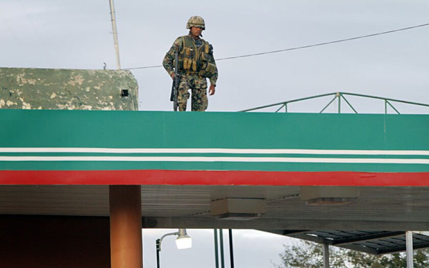 A Mexican soldier watches a key intersection that leads directly to the U.S. outside the Mexican city of Reynosa in 2010.