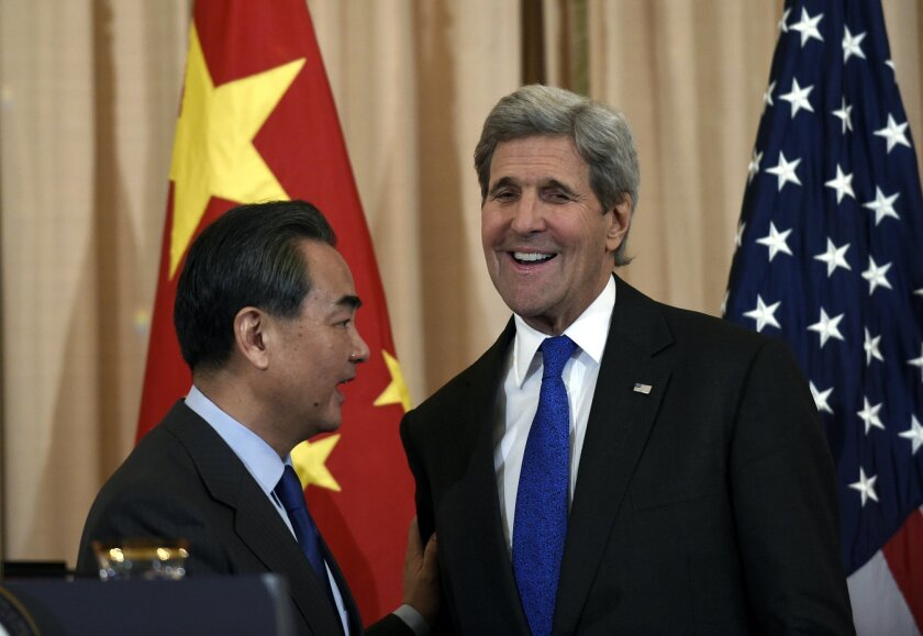 Secretary of State John Kerry, right, talks with with Chinese Foreign Minister Wang Yi, left, as the end of their media availability at the State Department in Washington, Tuesday, Feb. 23, 2016.(AP Photo/Susan Walsh)