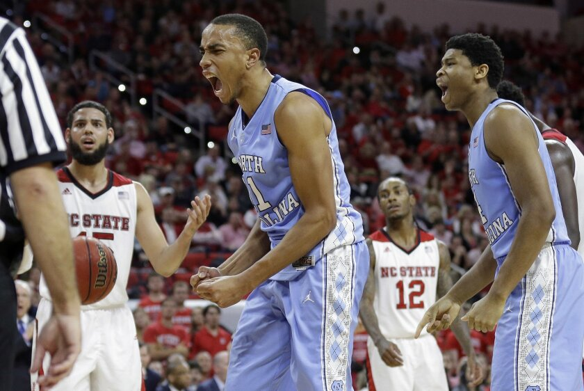 North Carolina's Brice Johnson, center, and Isaiah Hicks, right, react following a play as North Carolina State's Cody Martin looks on at left during the second half of an NCAA college basketball game in Raleigh, N.C., Wednesday, Feb. 24, 2016. North Carolina won 80-68. (AP Photo/Gerry Broome)