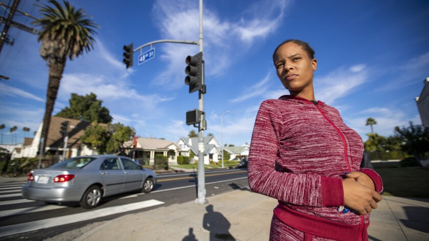 Precious McLaughlin stands at the busy intersection of West 48th Street and Arlington Avenue, near her South L.A. home.