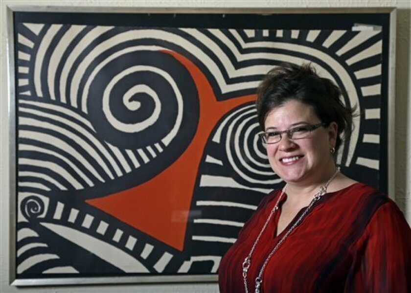 In this Wednesday, Nov. 28, 2012 photo, Karen Mallet stands in front of her Alexander Calder print in her Shorewood, Wis., home. Mallet bought the print for $12.34 at a Goodwill thrift store in Milwaukee. It turned out to be a lithograph by the American artist Alexander Calder worth $9,000. (AP Pho