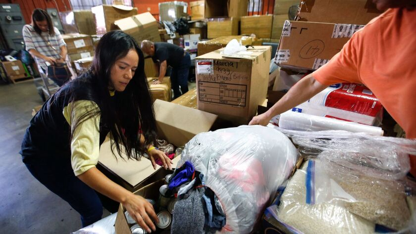 LOS ANGELES, CA-AUGUST 25, 2017-Venezuelan Tere Caicedo, left, helps fills up boxes with donated ite